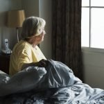 Senior woman sitting in a bedroom